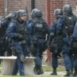 A Police swat team prepares to storm a building where a gunman is thought to be firing a weapon